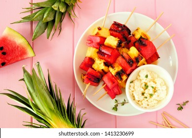 Grilled watermelon and pineapple fruit kabobs with feta. Above view on a pink wood background. Summer food concept.