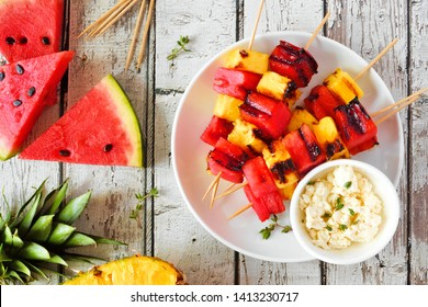 Grilled watermelon and pineapple fruit kabobs with feta. Top view on a white wood background. Summer food concept.