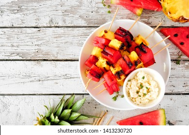 Grilled watermelon and pineapple fruit skewers with feta. Above view on a white wood table. Summer food concept.