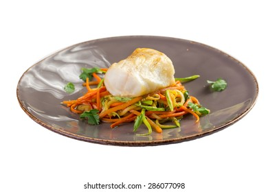 Grilled white fish fillet with a colorful salad isolated on white background