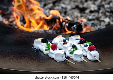 Grilled white marshmallows with berries and mint leaves on wooden skewers