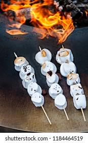 Grilled white marshmallows with chocolate crisps on wooden skewers