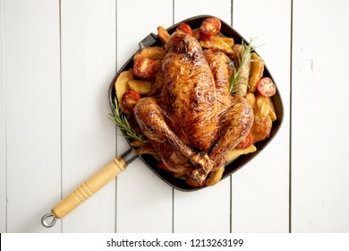 Grilled whole chicken in cast iron black pan. With potatoes, tomatos and rosemary herb. Placed in white wooden table. View from above. Shot with copy space.