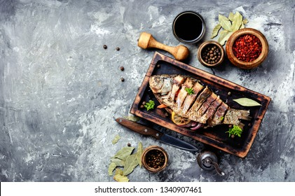 Grilled whole fish loaded with citrus, herbs and spices on rustic kitchen board
