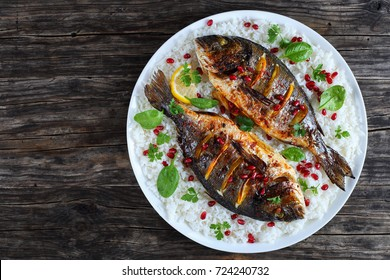 grilled whole fish loaded with fresh citrus, herbs spices and pomegranate seeds on bed of rice, on white plate on old dark wooden table, view from above