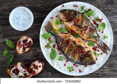 grilled whole fish loaded with fresh citrus, herbs spices and pomegranate seeds served with rice, on white plate  with spinach cream sauce on old dark wooden table, view from above, close-up