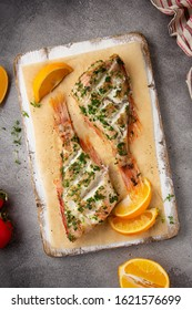 Grilled whole fish (perch, sea bass, redfish) with parsley and lemon (orange), delicious roasted food. Healthy diet