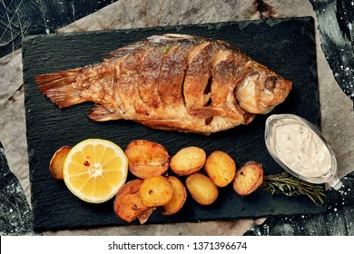 Grilled whole fish Served with baked potatoes, lemon and sauce. Top view.