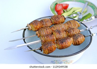 Grilled whole potatoes with bacon on skewers.  Served with sliced fresh vegetables