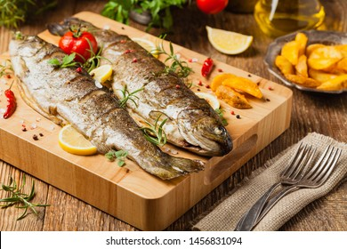 Grilled whole trout. Served with baked potatoes. Front view.
