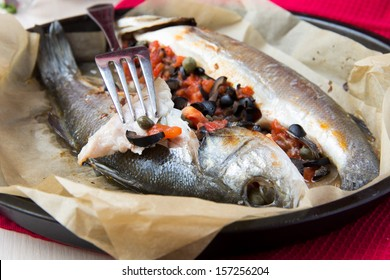 Grilled whole white fish, sea bass stuffed with black olives, capers and tomatoes, tasty dish
