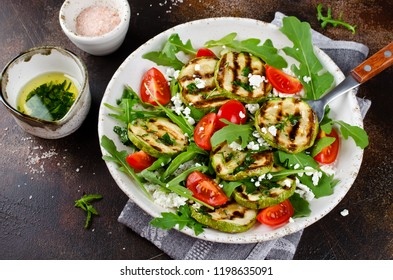 Grilled zucchini with arugula, tomatoes and cottage cheese. Salad with garlic dressing