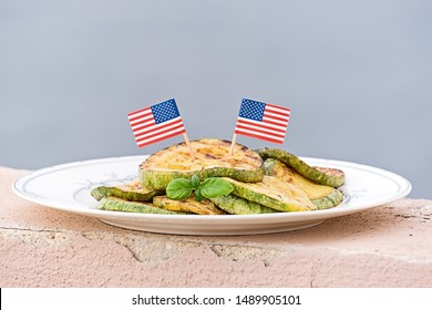 Grilled zucchini medallions on white plate with USA flags against sky. Thanksgiving dinner concept