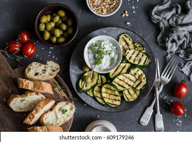 Grilled zucchini, olives, tomatoes, ciabatta - simple snack or appetizer. Mediterranean style food. On a dark background, top view. Flat lay
