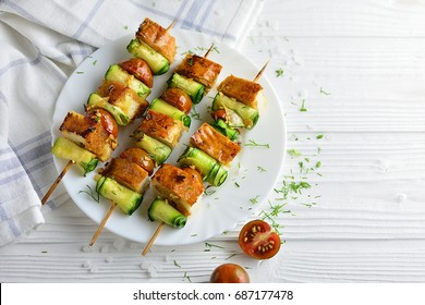 Grilled zucchini on skewers with tomatoes and toast on a white plate and light background