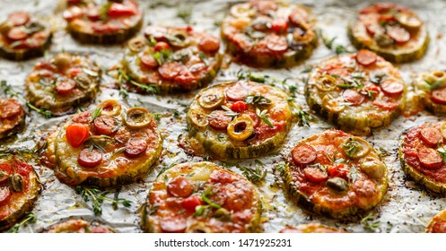 Grilled zucchini slices with addition of mozzarella cheese, sausage, green olives, capers and herbs on white baking paper, cloys-up. Delicious appetizer, zucchini pizza bites