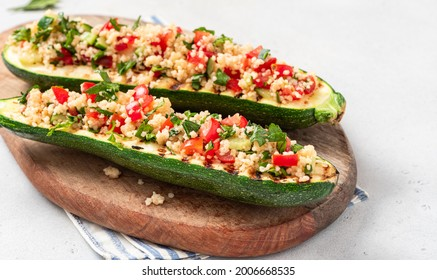 Grilled zucchini stuffed with couscous, tomatoes, cucumber and parsley. Vegan stuffed zucchini on a cutting board. Vegetarian food.