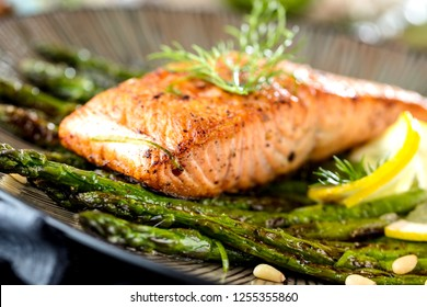 Grillen salmon filet and asparagus on wooden table close up