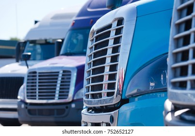 Grilles of different models of big rig semi trucks which stand in row on the truck stop parking waiting to continue delivery cargo