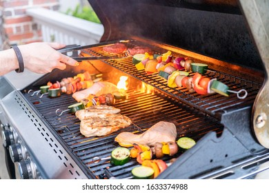 Grilling an Atlantic salmon, chicken breast, vegetable skewers, and vegetarian burgers on an outdoor grill.