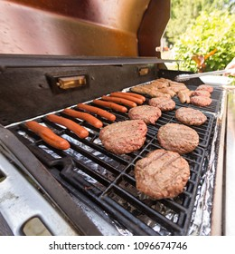 Grilling Burgers and Dogs on a gas grill on a sunny day in the summer