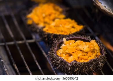 Grilling and burn sea urchin on flaming fire at Hokkaido morning market. Freash and Delicious seafood breakfast.