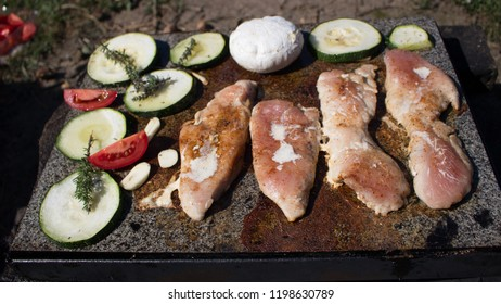 Grilling chicken breast and vegetables on the stone, hot meat dishes