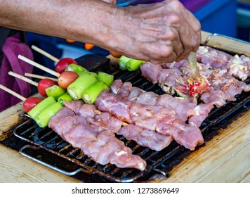Grilling chicken kabobs on flaming grill, chicken shish kebab on bbq grill in sauce on skewers with tomatoes and peppers
