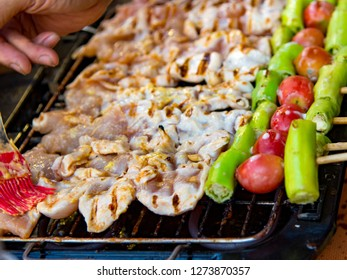 Grilling chicken kabobs on flaming grill