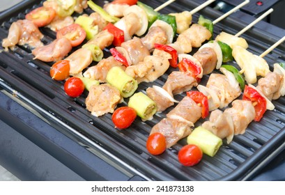 Grilling chicken on barbecue grill.