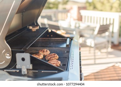 Grilling classic burgers on outdoor gas grill in the Summer.
