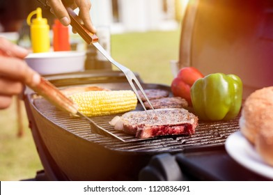 Grilling food at garden party. Closeup of fork being used for baking beef and corn on barbeque with bell peppers. Close up of grilled meat with vegetable over the coals on a bbq.