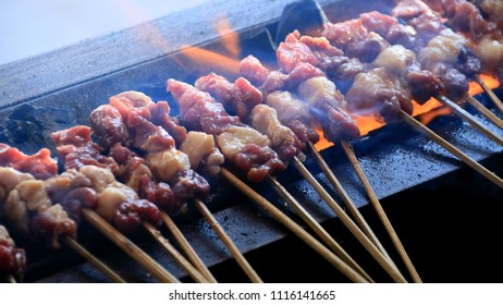 Grilling goat satay over charcoal.
