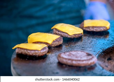 grilling hamburger patties with cheese in smoke open air