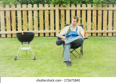Grilling: Man In Backyard Sitting By Grill