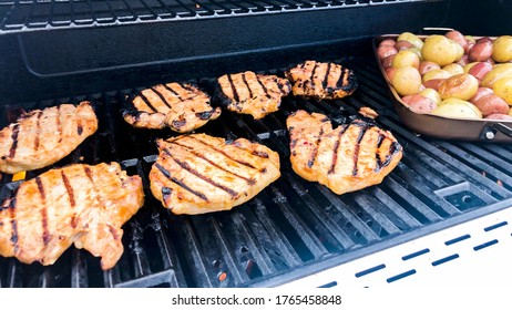 Grilling marinated chicken and small potatoes on an outdoor gas grill.