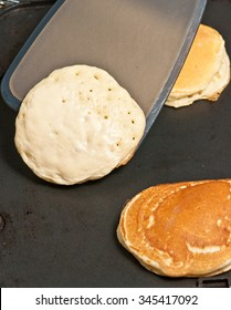 Grilling pancakes on solid grill and flipping with a spatula