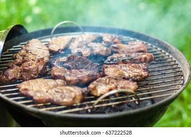 Grilling pork meat with barbecue stuff. Horizontal close up shot