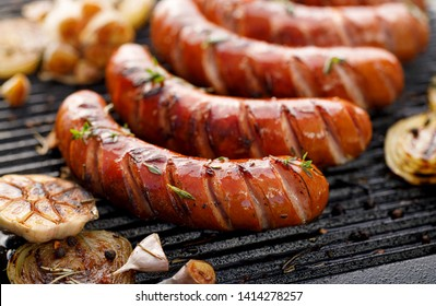 Grilling sausages with the addition of herbs and vegetables on the grill plate, close-up. Grilling food, bbq, barbecue