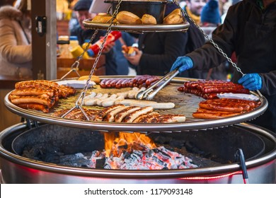 Grilling sausages on barbecue grill at a food stall of Christmas market winter wonderland in London