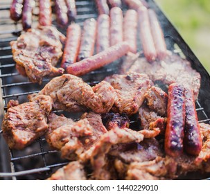 Grilling sausages on barbecue grill. Pork sausage and steak in smoke. Close-up view & Selective focus.