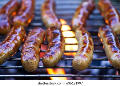 Grilling sausages on barbecue grill. BBQ in the garden. Bavarian sausages.