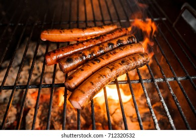 Grilling sausages on barbecue grill. Juicy meat. Selective focus