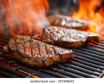 grilling steaks on flaming grill and shot with selective focus