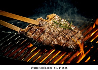Grilling a tasty tender marinated t-bone steak seasoned with fresh rosemary on a barbecue fire with hot fiery coals in a close up view
