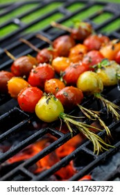 Grilling tomato skewers, skewers of colorful cherry tomatoes studded on rosemary sprigs with the addition of aromatic spices and sea salt on a grill plate, outdoors. Vegan grilled food