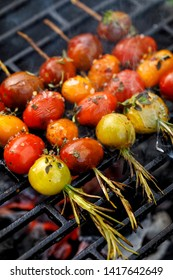 Grilling tomato skewers, skewers of colorful cherry tomatoes studded on rosemary sprigs with the addition of aromatic spices and sea salt on a grill plate, outdoors, close-up. Vegan grilled food