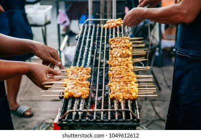 Grillled barbecue pork satay skewers on charcoal grill stove in street food market, Uthai thani - Thailand