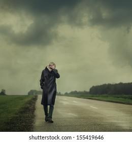 grim man in a black cloak walking on the road alone
