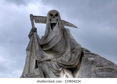 Grim reaper Death personified as a skeleton with a cloak and scythe. This picture of weathered sculpture was taken in a French cemetery. This tombstone was built in memory of a sailer.